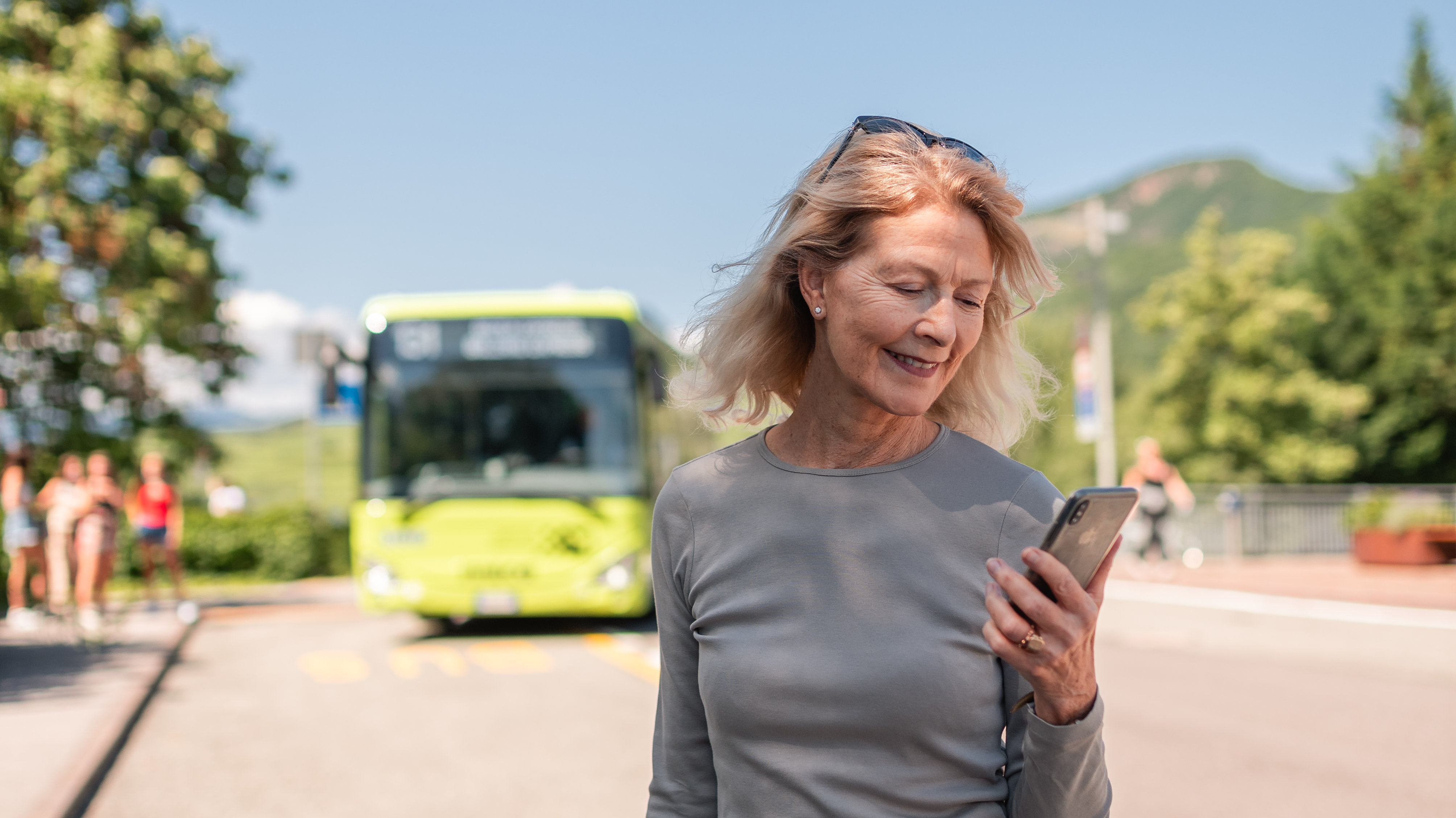 Woman with mobile next to a bus